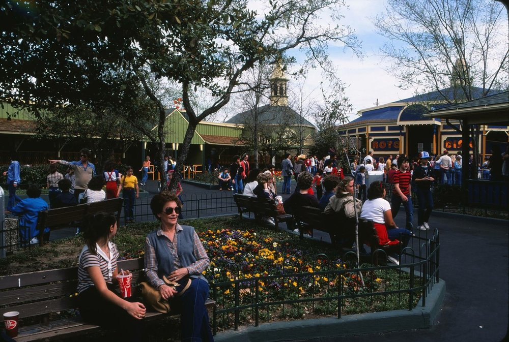 Guests enjoying the park's Goodtimes Square area with the green Bumper Cars building in the background. Credit: Six Flags Archives