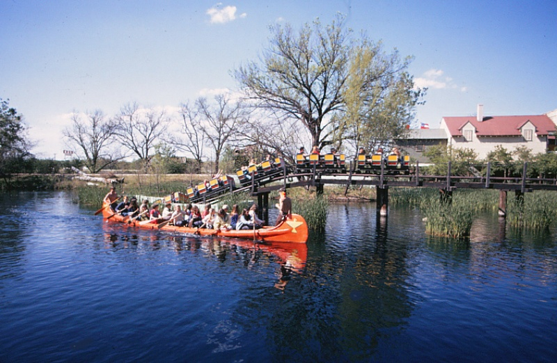 Runaway Mine Train emerges from its underground tunnel with Caddo War Canoes floating by. Credit: Six Flags Archives