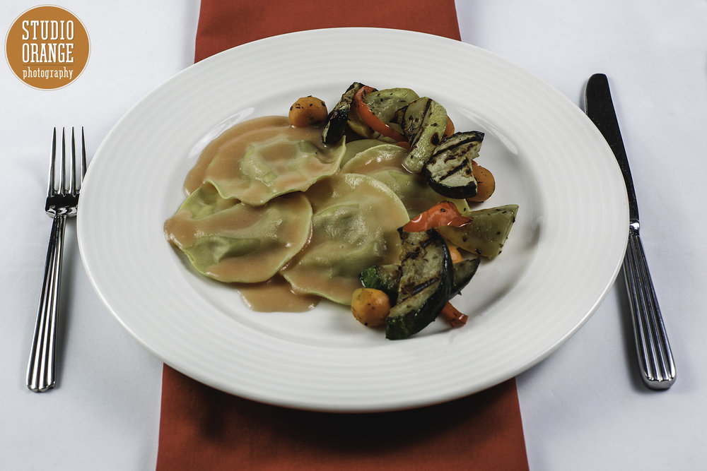 Mushroom Ravioli - Vegetarian Mushroom Ravioli in a blood orange champagne sauce. Served with grilled vegetable medley.