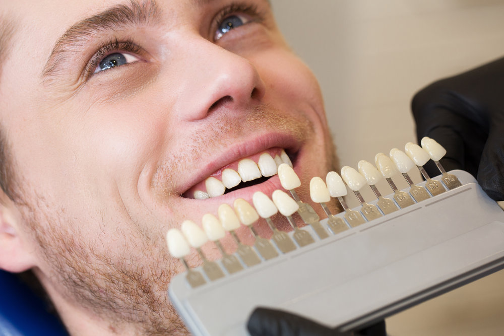 CloseupportraitofYoungmanindentistchairCheckandselectthecoloroftheteeth.Dentistmakestheprocessoftreatmentindentalcli.jpg