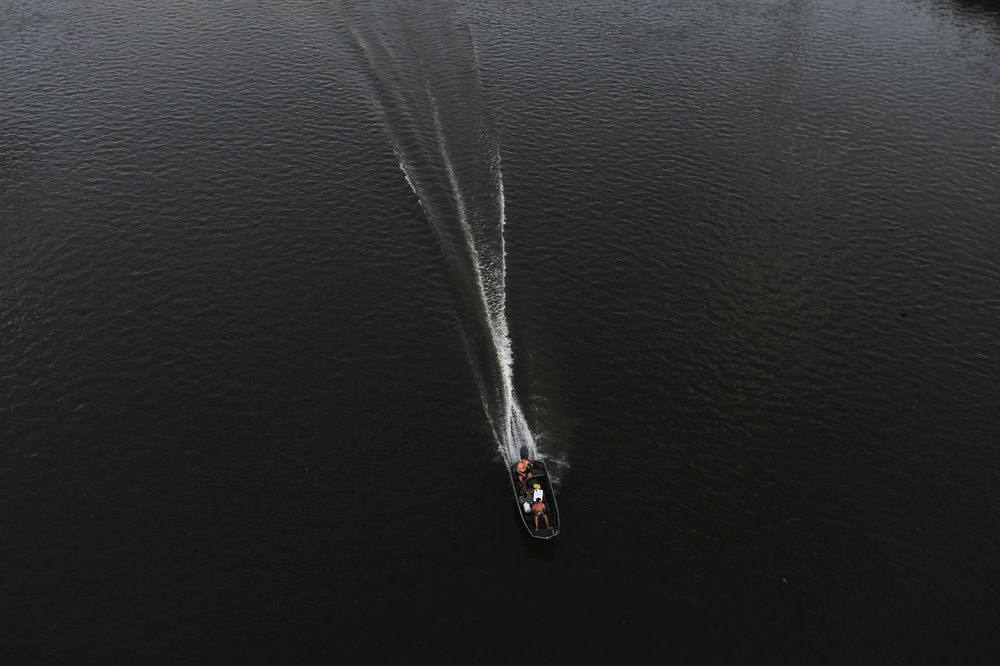 A fishing boat cuts a wake in the dark waters of the Cumberland seen from the Shelby Street Pedestrian Bridge in Nashville, Tenn.