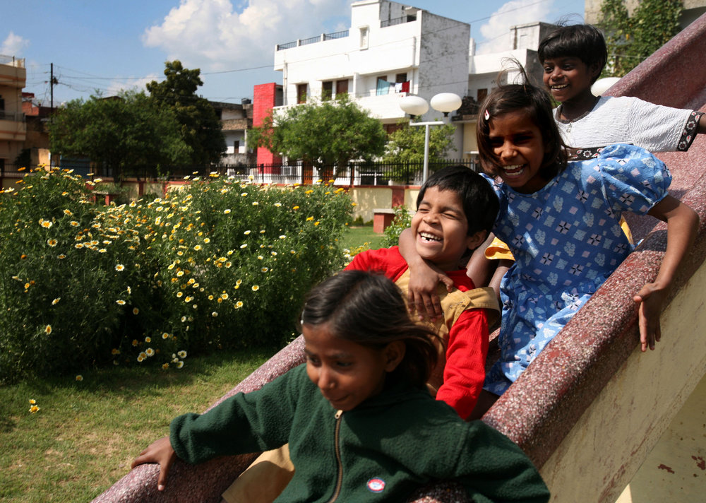 Kajal goes down the slide at the neighborhood park with the help of her children from the Snehlayam Shelter Home run by the Society of Underprivileged People Friday, March, 2, 2007 in Allahabad, India.