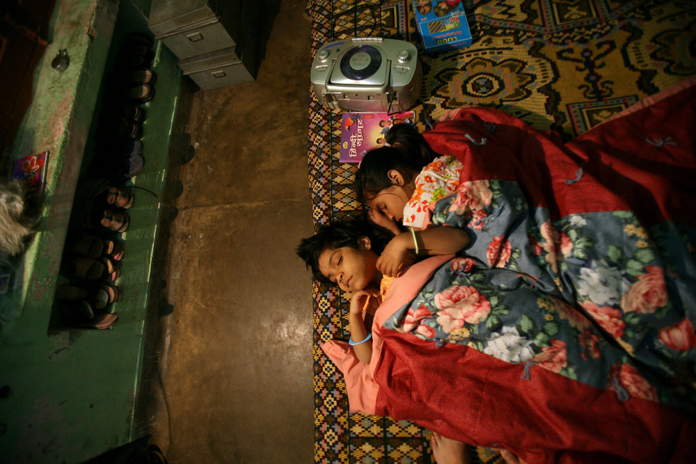 "Kajal falls asleep curled next to her ""sister"" Madhu, right, at the Snehlayam Shelter Home Monday, March, 5, 2007 in Allahabad, India."