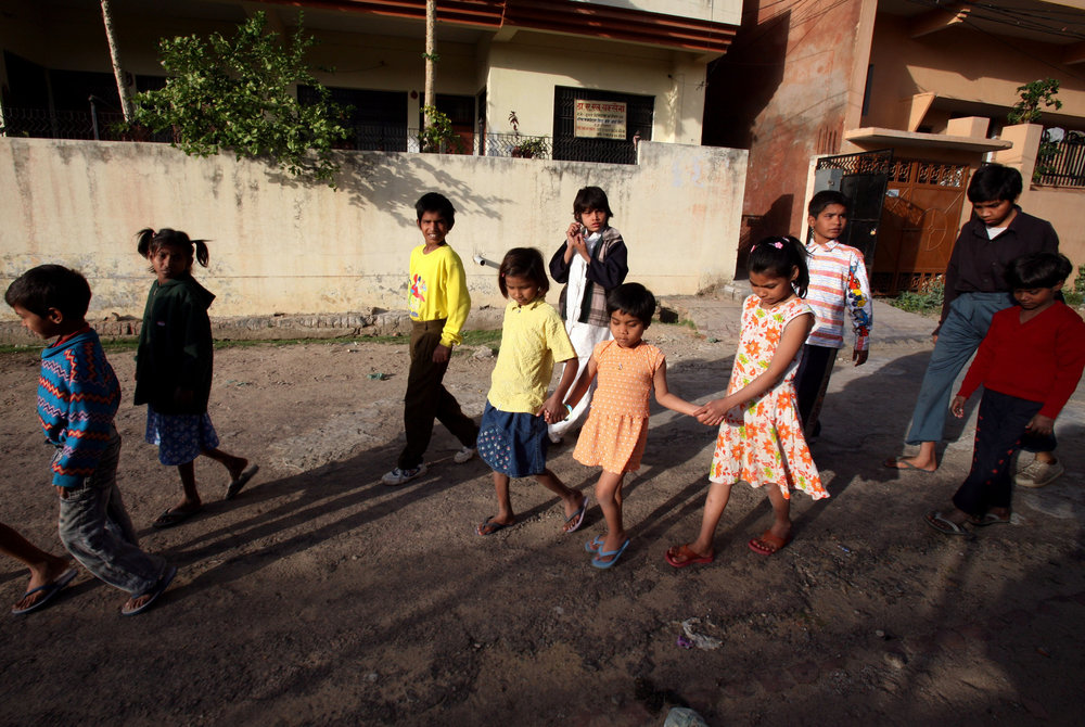Kajal walks with the help of fellow children from the Snehlayam Shelter Home to the neighborhood park Monday, March, 5, 2007 in Allahabad, India.