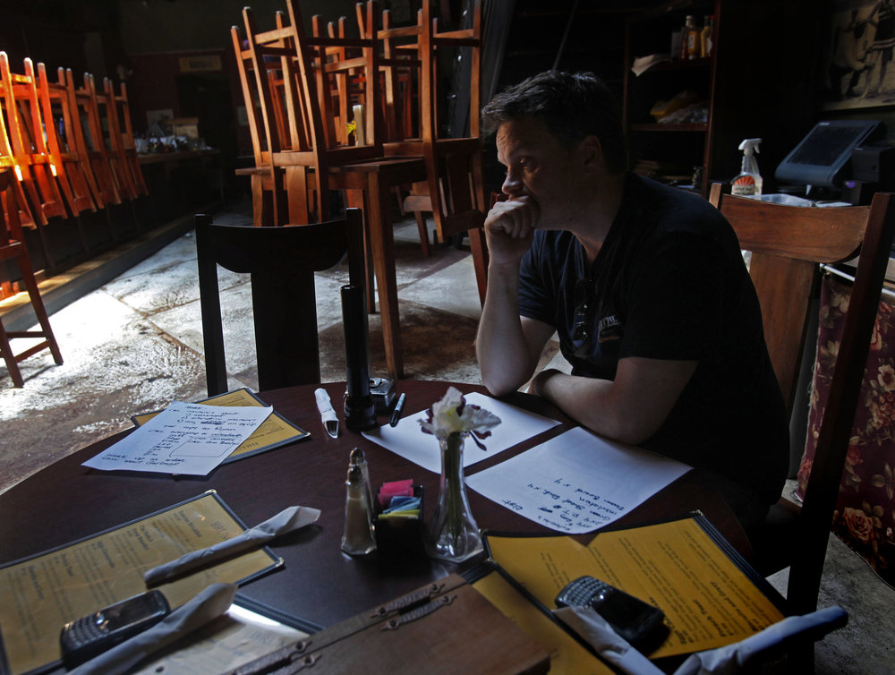 "Shawn Courtney, co-owner of Past Perfect, sits in his restaurant and tries to figure out his losses after their downtown building flooded, May 6, 2010 in Nashville, Tenn. ""We're hurting, "" said Courtney, unsure if he can re-open. Past Perfect is his first restaurant."