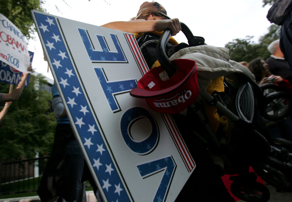 An Obama supporter carries a sign on entering the quad before the debate at Belmont University in Nashville, Tenn.