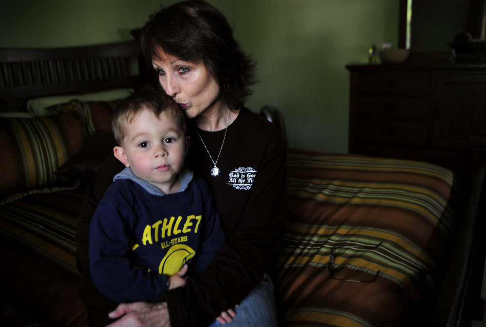 Sherry Wilson, sits in her son Danny Tomlinson's room with Tomlinson's nephew, age 3, April 21, 2011 in Pegram, Tenn. Tomlinson died while driving during the 2010 flood. Wilson and her husband moved into her son's house and have kept his bedroom a shrine. Her grandchildren help her cope with the loss.