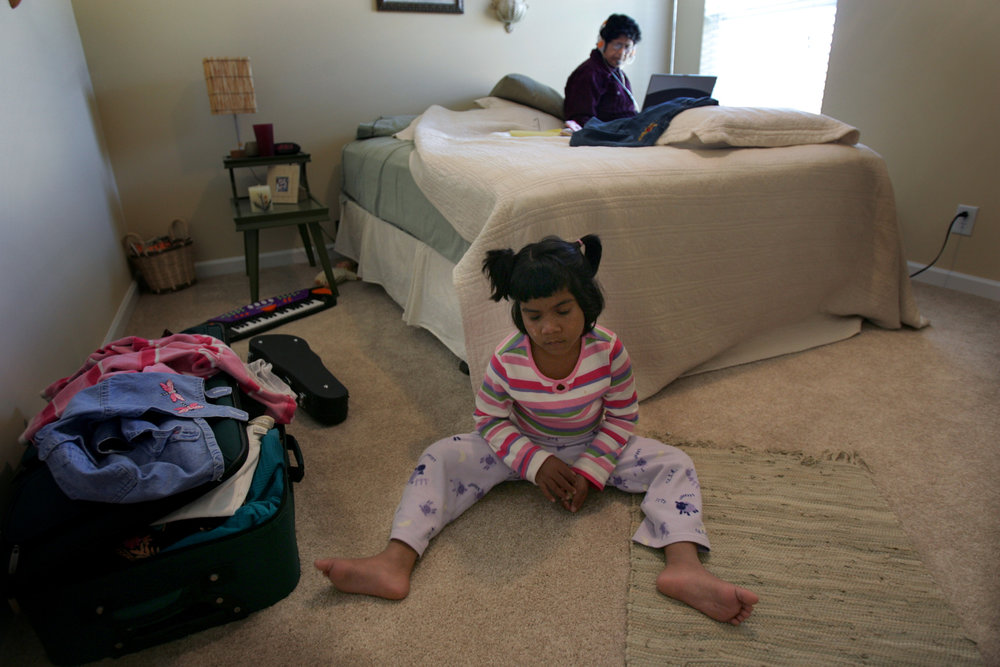 Kajal plays in her room at a new host family's house while guardian Grace Zaidi emails her husband in India November 15, 2007. The Zaidis co-founded S.O.U.P, the Society for Underprivileged People, the organization that rescued Kajal.
