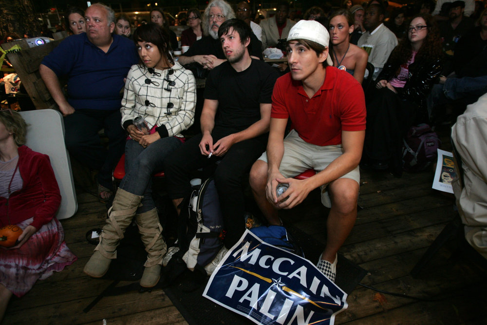 Jack Young with a McCain sign at his feet watches the beginning of the town hall debate on TV at nearby Bongo Java coffee shop.