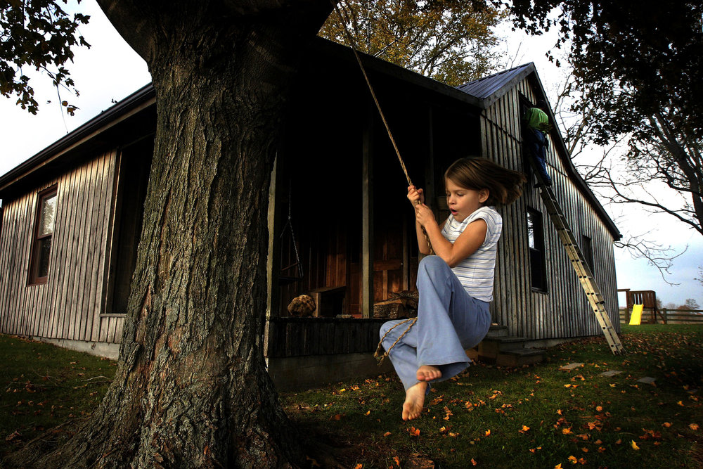 Anna Stewart Burdette, 7, swings on a rope swing in the front yard while her father paints an upstairs window of their house. The Burdettes were given an abandoned two room board and battan house which they refurbished in Marion County.