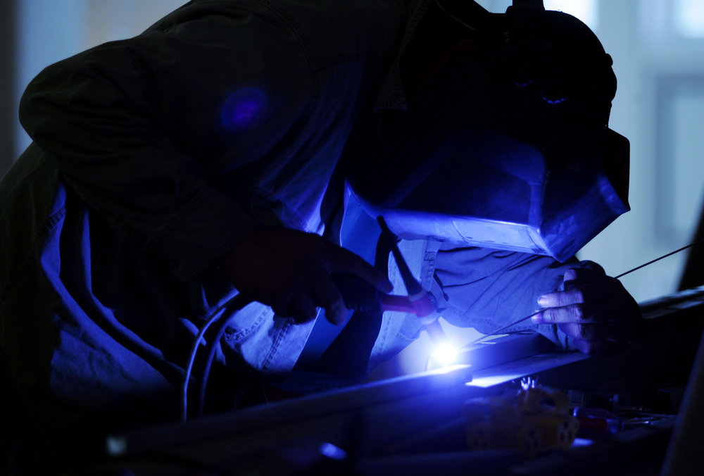 Cristobal Gomez of Ameriprise Company welds pieces of metal while doing architectural metalwork.