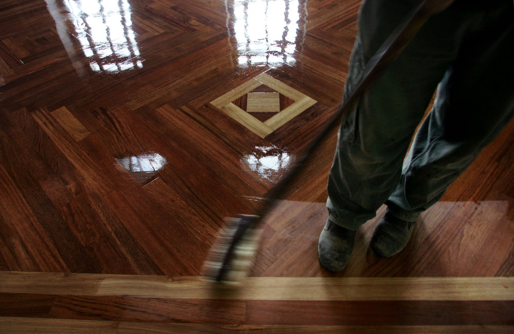 Mark Hollaway of Floor Works adds a final coat of polish onto the Brazilian cherry wood floors.