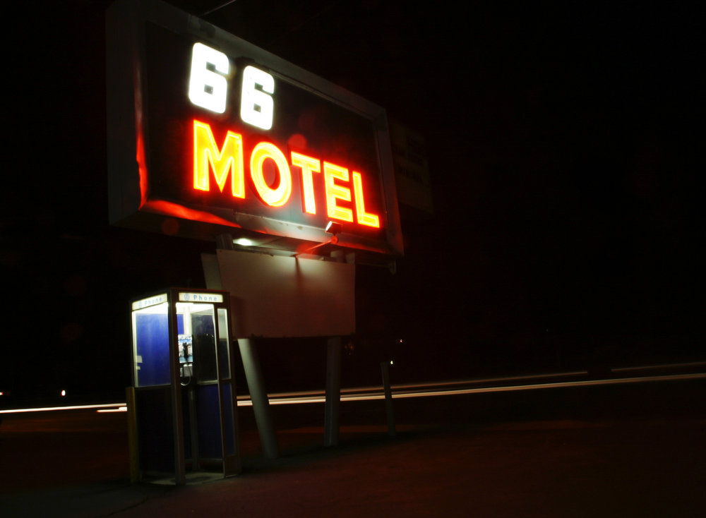 Car headlights mark Route 66 as they go by the 66 motel in Flagstaff, Arizona at night.