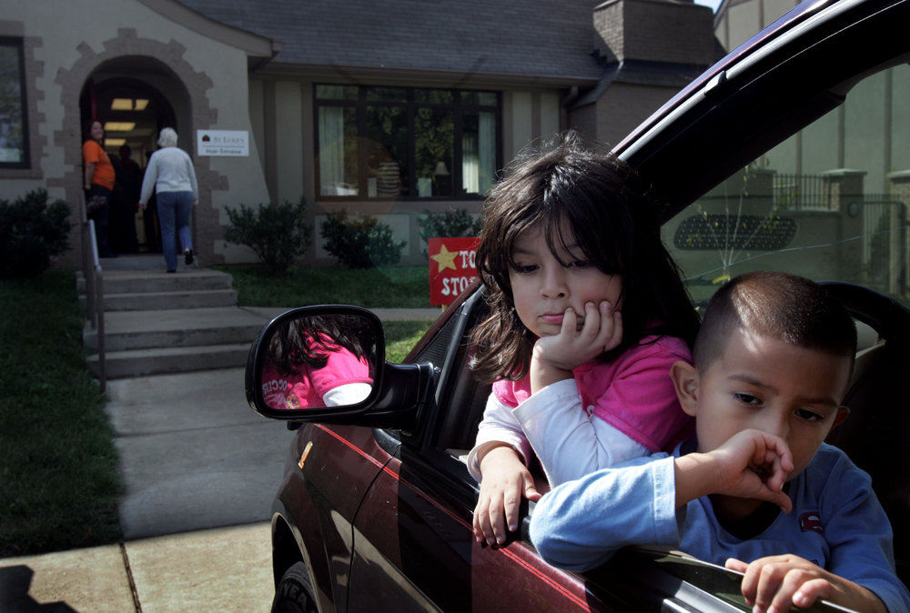Natalie Hernandez, 3, with cousin Renee Cordero, wait in the car at St. Luke's Community House for their parents to pick up from the food bank in Nashville, Tenn.
