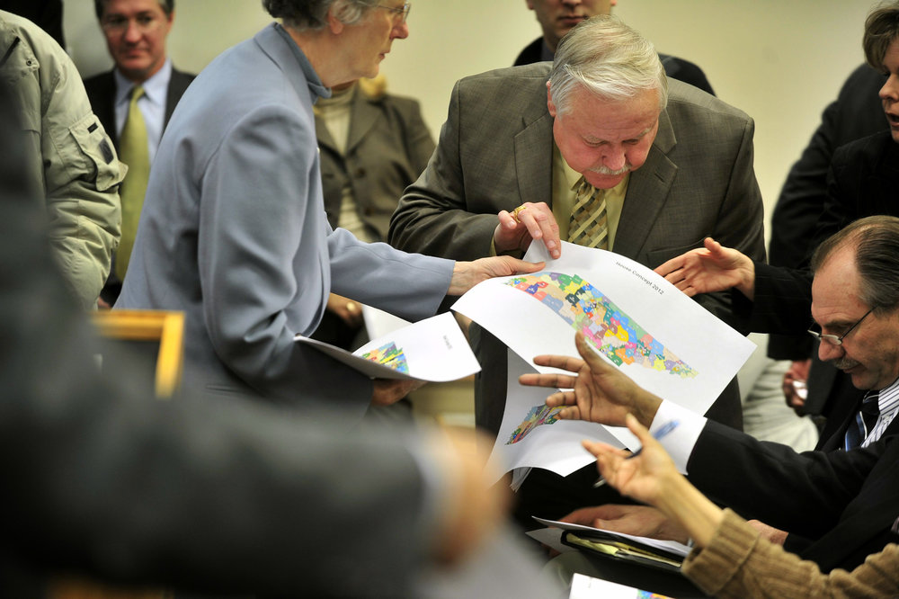Attorney Sally Swaney hands out redistricting maps to a crowd of lawmakers including Rep. Gary Moore D-Joelton, and Rep. Mark Pody R-Lebanon, right. The map was a controversial plan proposed by Republican lawmakers January 4, 2012 Nashville, Tenn.