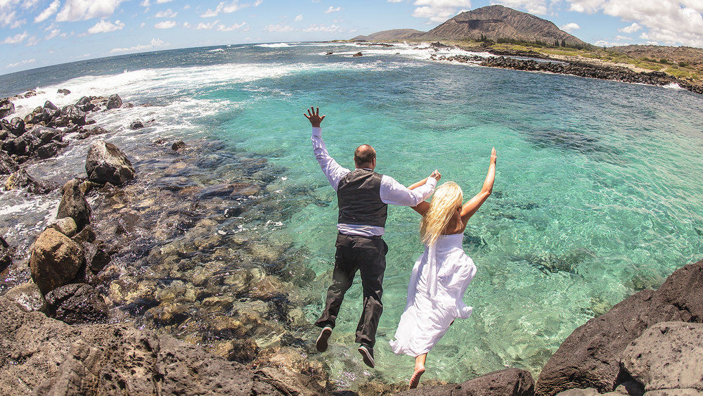 Jumping into the cool blue during a post wedding session at Ka Iwi Hiking Trail, Hawaii.