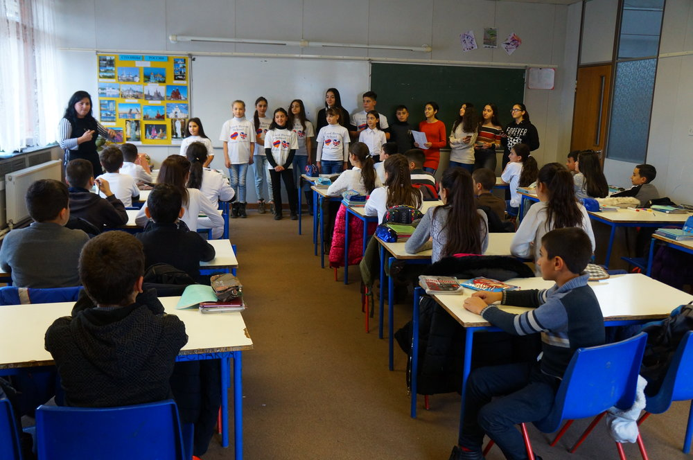 """Ohanna practicing the school anthem with her students.  The anthem is a reflection of the school's past and a """"thank you"""" to the British people who supported the rebuilding of the school."""