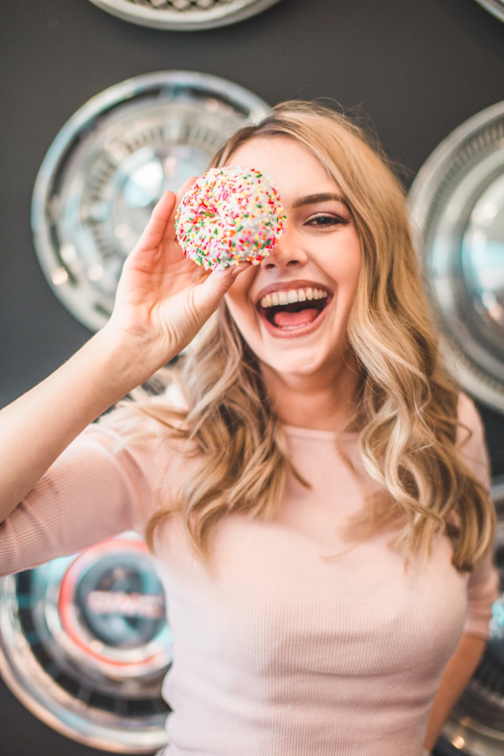 Fun image of a young woman holding a sugary donut over one eye and smilling