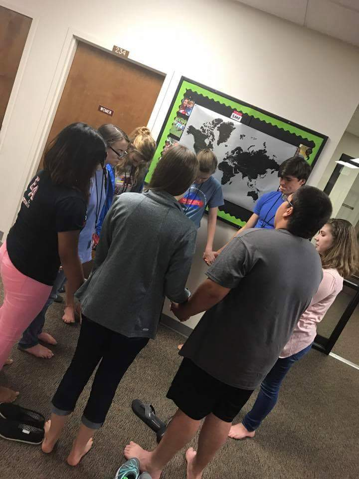 Christian Youth In Action ®  missionaries take time near a map at training to pray over the country of North Korea.
