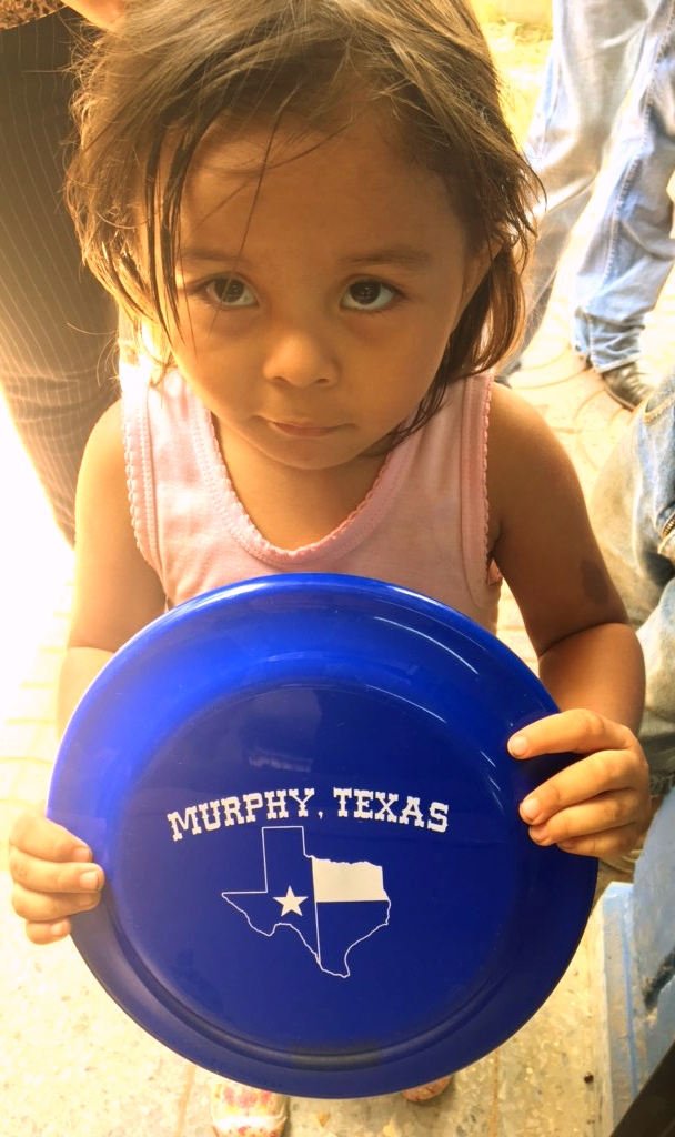 A child holds a frisbee from the City of Murphy.