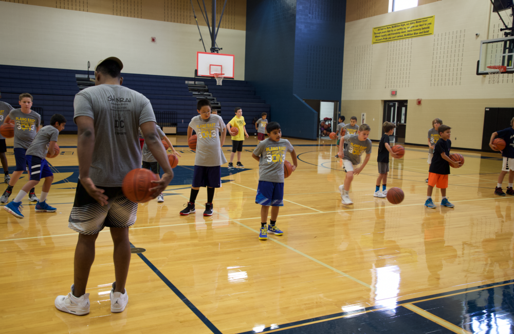 Camp assistant, Devin Gifford, warms up campers at the beginning of a session with ball handling drills.