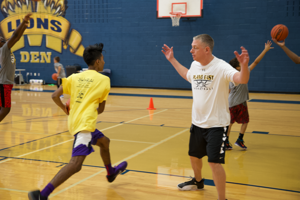 Coach Derrick Richardson works with a camper to improve his Euro step intended to allow an offensive player to evade a defender with a change of direction.