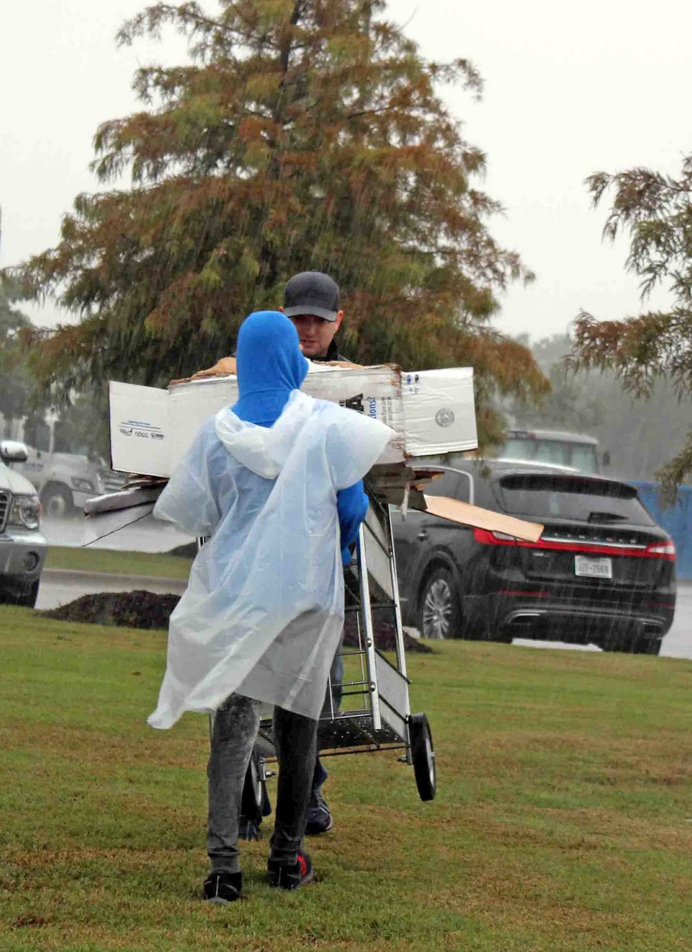 Bryce Gullatt, City of Murphy staff and Green Team member, works against wind and rain with a student volunteer from the Murphy Middle School Environmental Club to move an unwieldy cart of cardboard to be recycled.