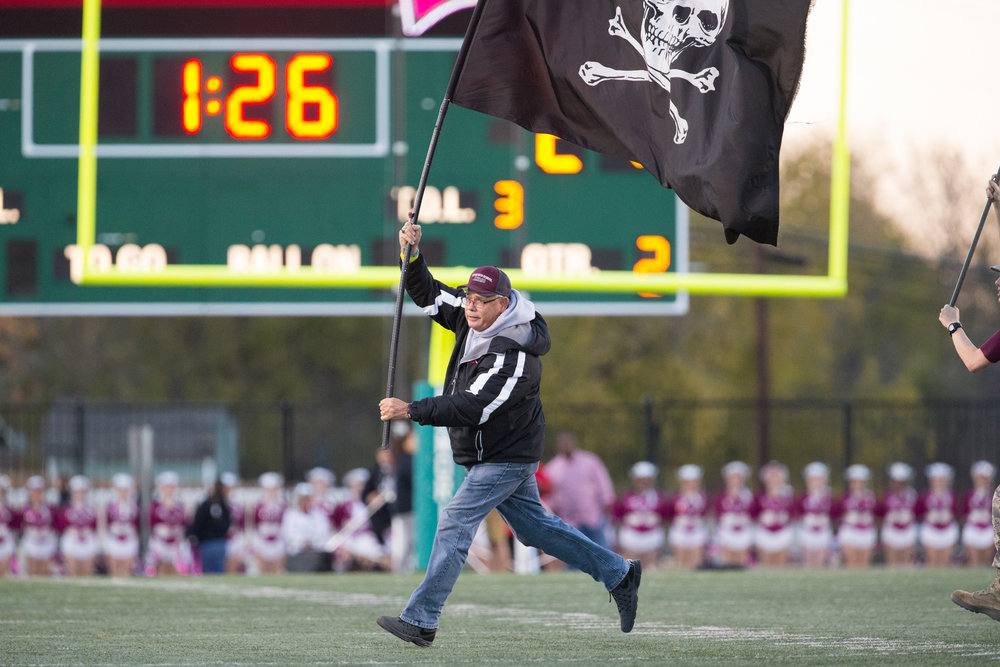 Wylie principal Virdie Montgomery runs with the flag on the field after a Pirate score.
