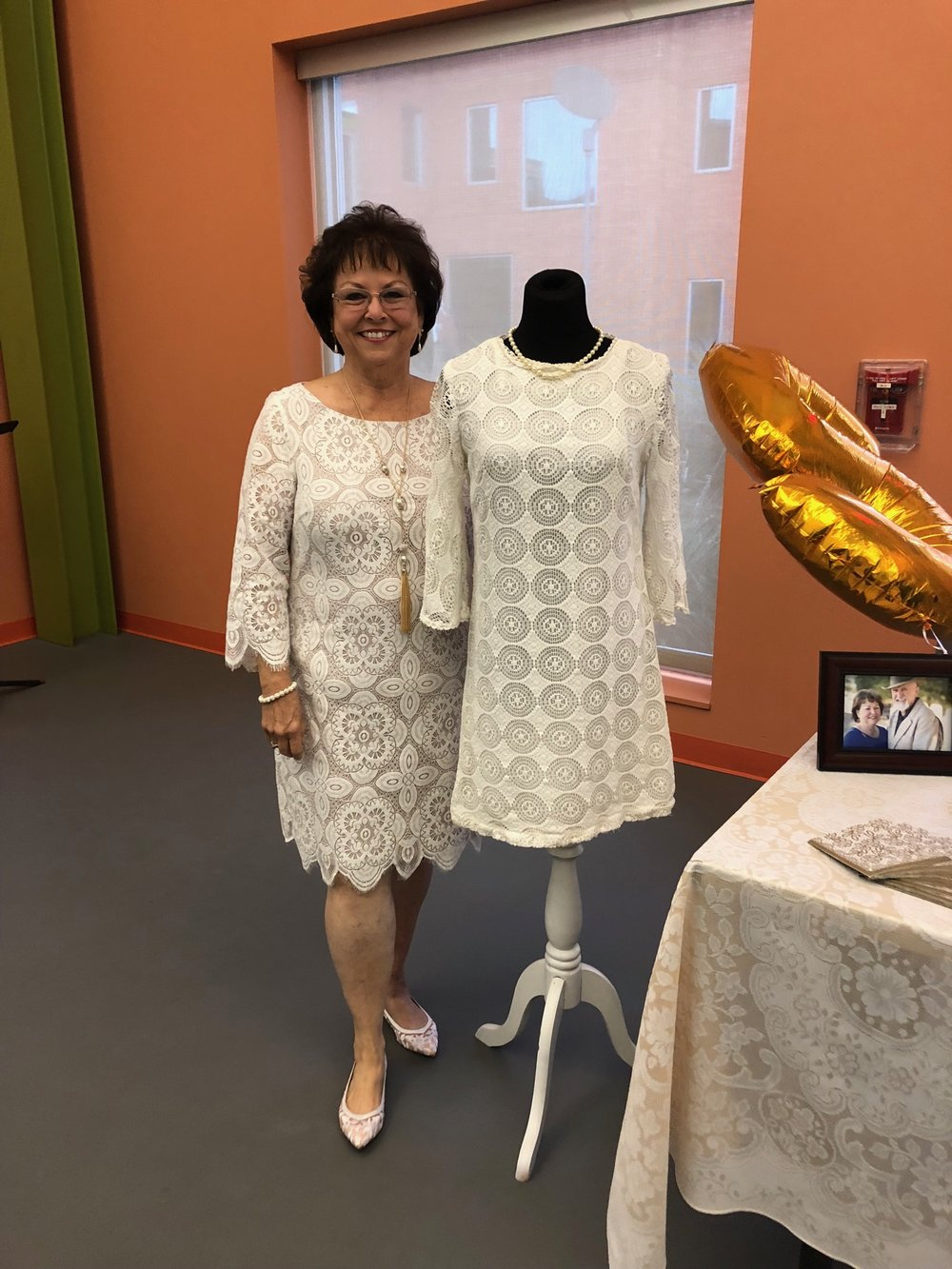 Vickie Tucker standing next to her wedding dress at their 50thanniversary party.