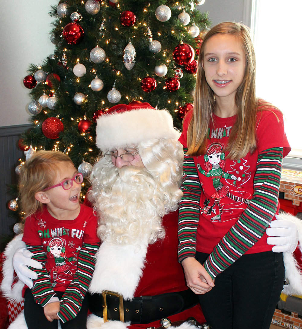 Sisters, (left) Arianna and (right) Aubrey Leverton enjoy visiting with Santa.