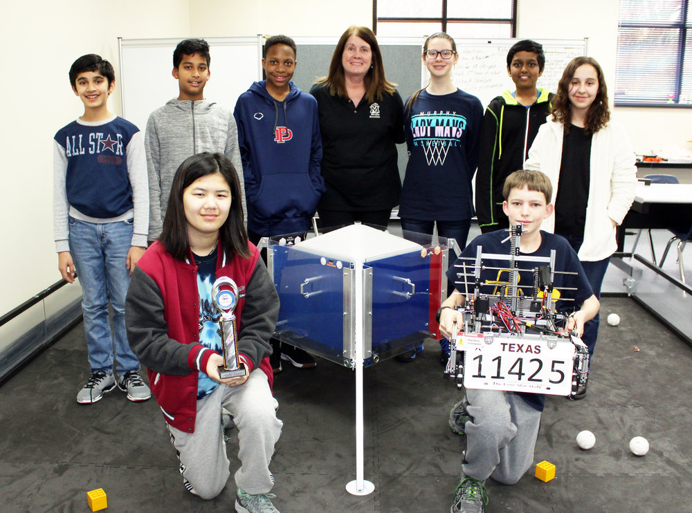"MMS robotics team during their weekly, after school meeting. (Front row, from left) Lexi Pietrasik holding the first place trophy and Justin Simms holding ""Murphy"". (Back row, from left)"