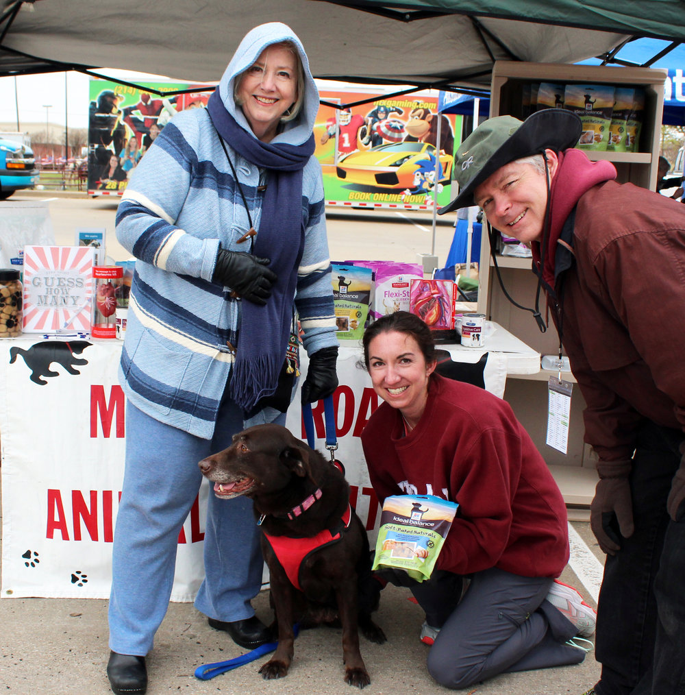 Murphy resident Esther Towles and her British Chocolate Labrador rescue dog Molly, visit with Jim Moebius, veterinarian and Stephanie Carroll, veterinary technician from Murphy Road Animal Hospital.