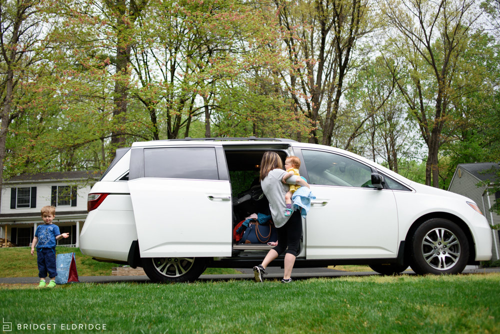mom multitasks getting two kids out of the van