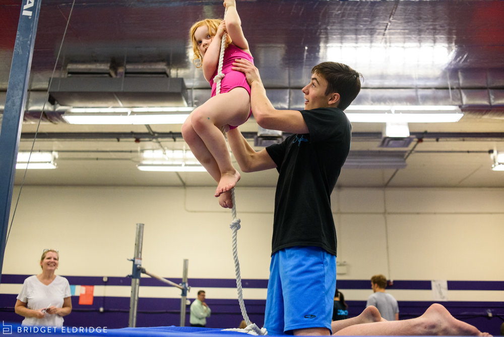 little girl climbs rope as mom watches on proudly