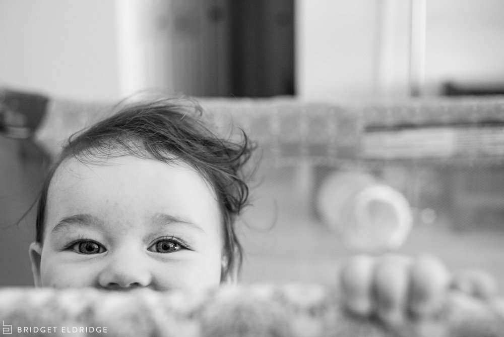 baby plays peek-a-boo from pack-and-play