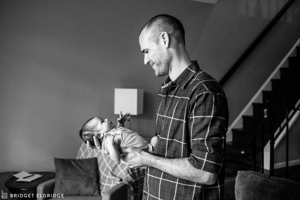 dad rocks newborn daughter