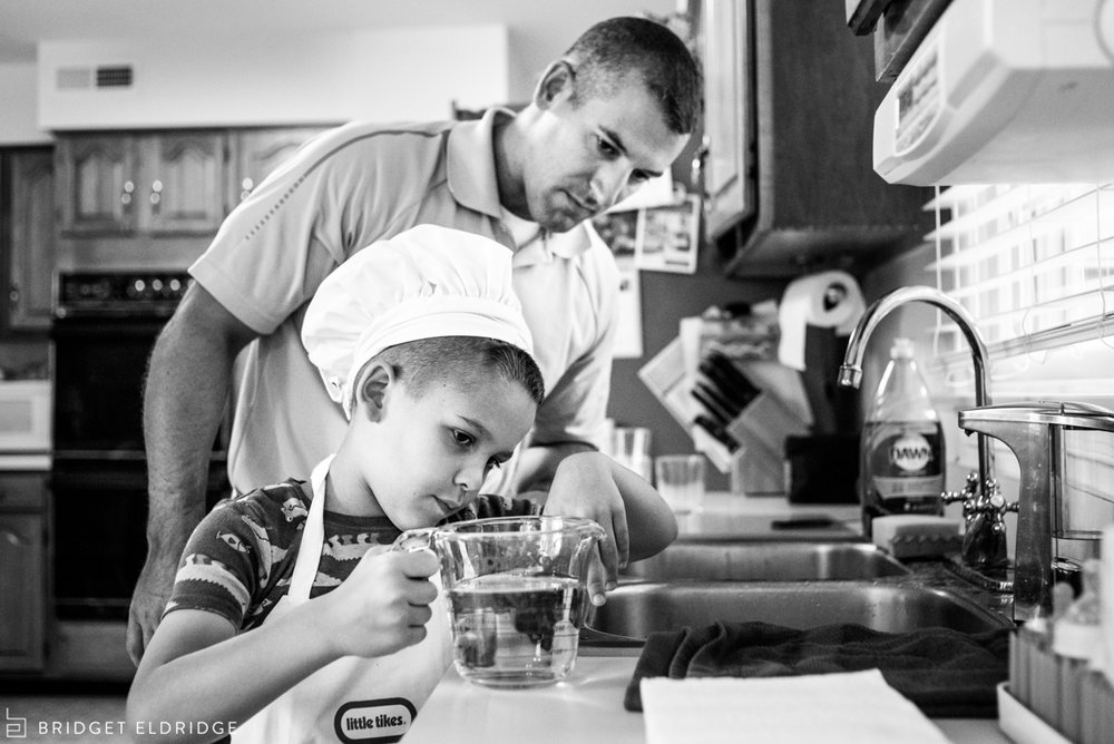 dad and son measure water for pancake mix