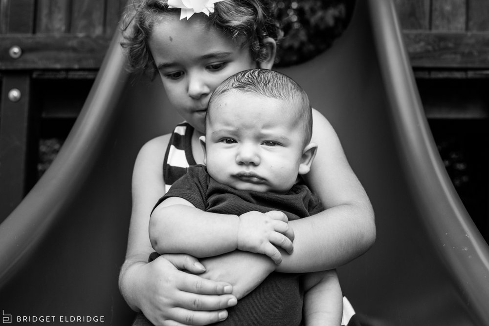 big sister holds her baby brother as they go down the slide