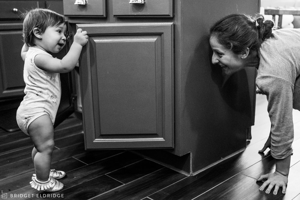 toddler plays peekaboo with mom
