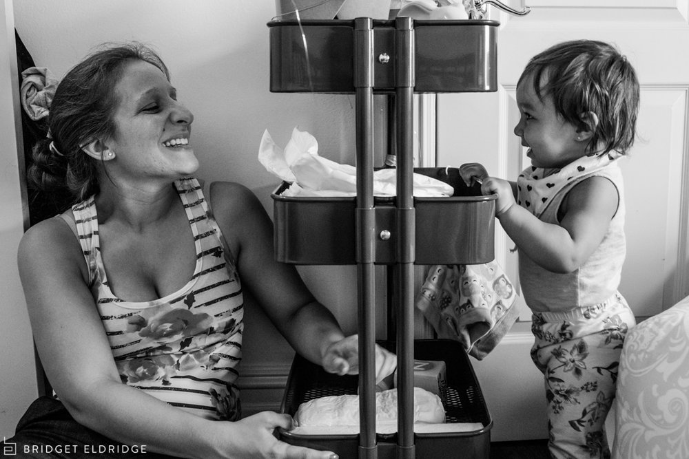 mom laughs as her daughter tries to pull over the diaper cart from ikea