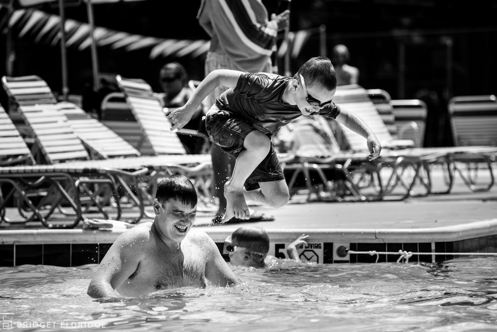 son jumps off of father's shoulders at the waynewood pool