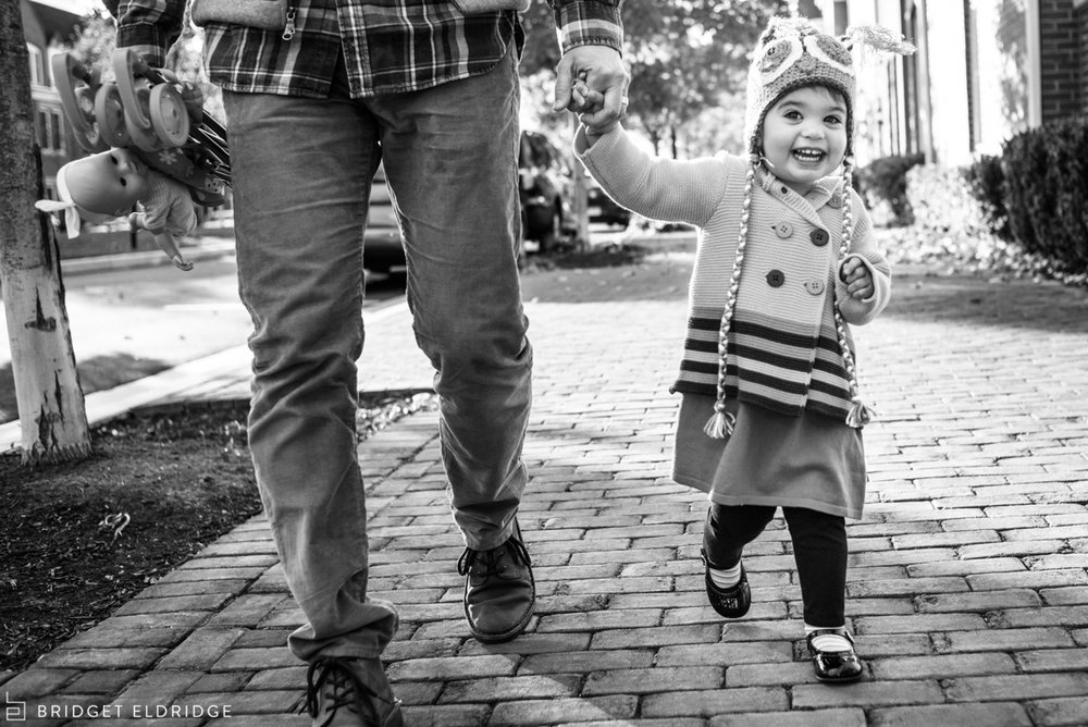 little girl smiles as she goes on a walk with her father