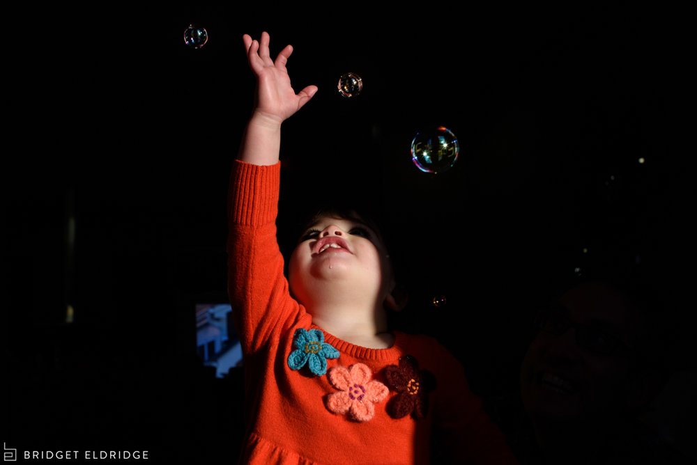 toddler tries to catch bubbles