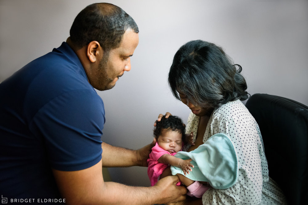 mom hands dad their newborn daughter after a feeding