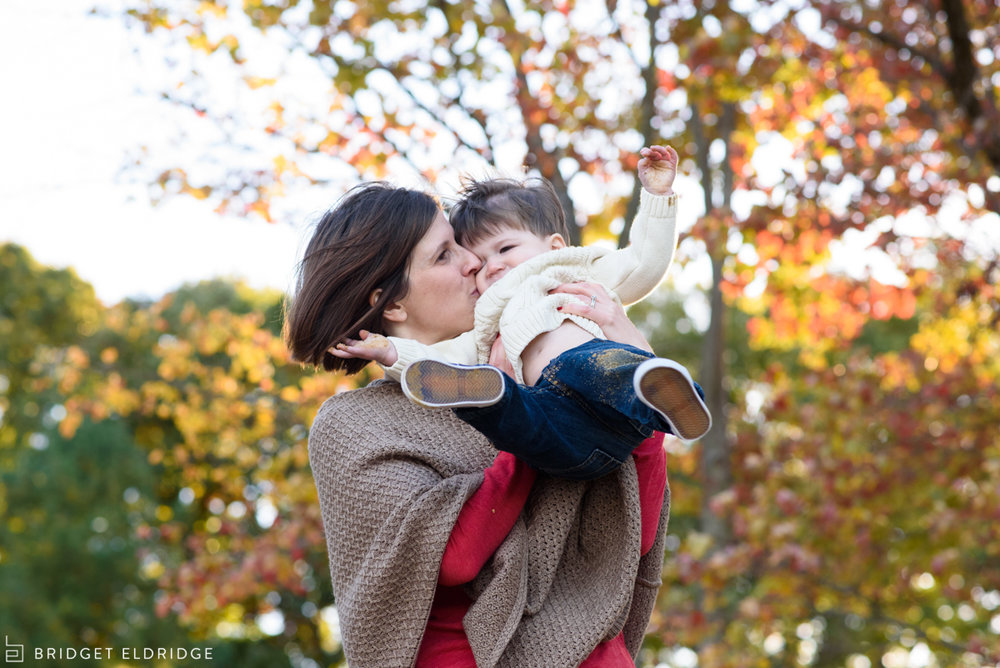 mom kisses her son in the fall leaves
