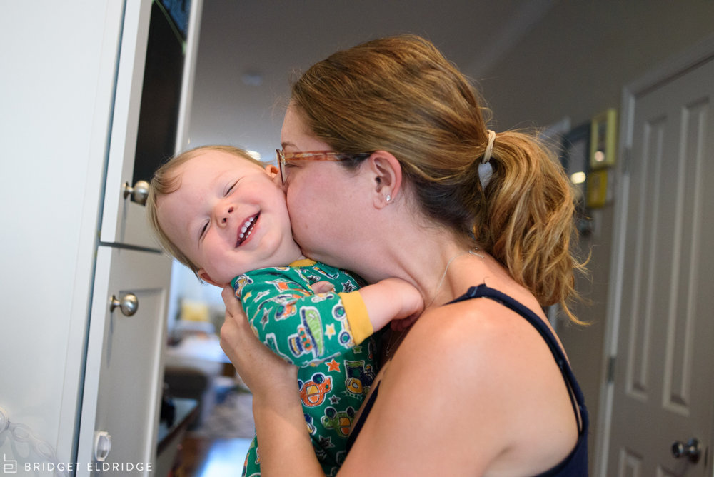 Mom kisses her 1 year old son in their home in Washington DC's Capitol Hill neighborhood.