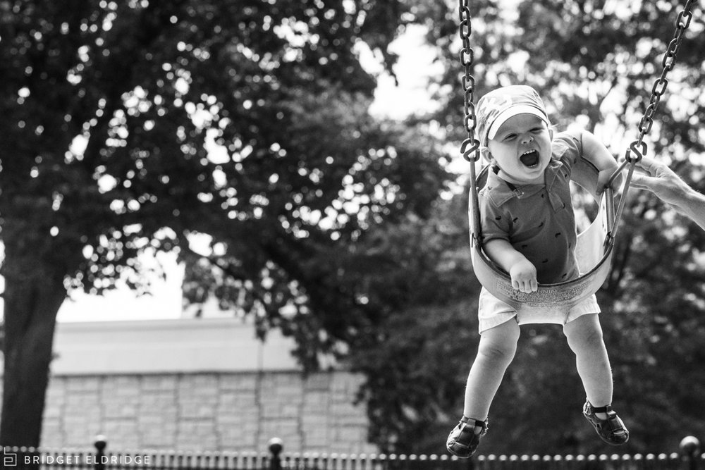 Dad pushes his son on a swing at a park on Capitol Hill.