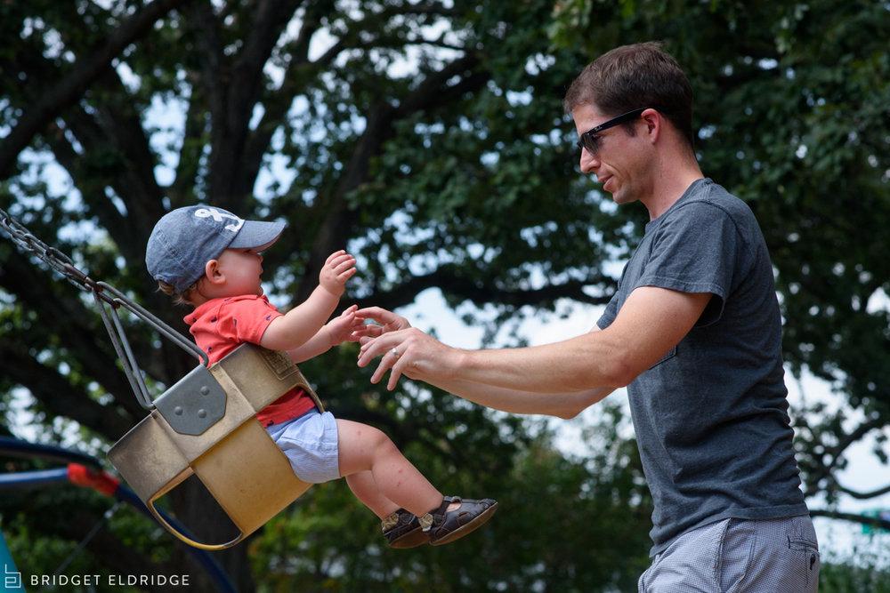 Dad pushes his toddler at a Washington DC public park.