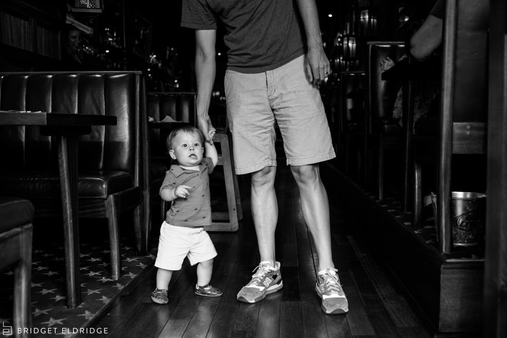 13 month old holds dad's hand as the family leaves Boxcar Tavens