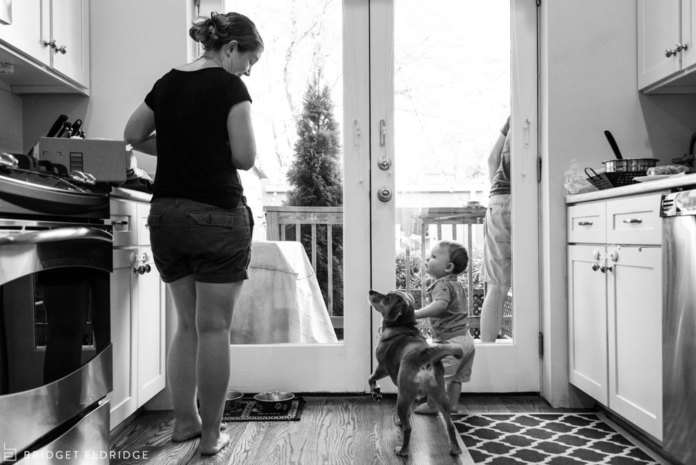 Boy and his dog look to mom as she cooks dinner.